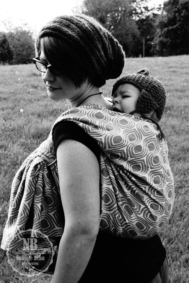 Opis fotografije za slijepe i slabovidne osobe. [Na crnobijeloj fotografiji žena nosi bebu u marami na leđima. U pozadini je livada. Oboje nose ručno pletene kape. Žena zamišljeno gleda prema dolje a beba joj umorno zijeva na leđima. Tkana marama ima uzorak stiliziranog paunovog oka.]